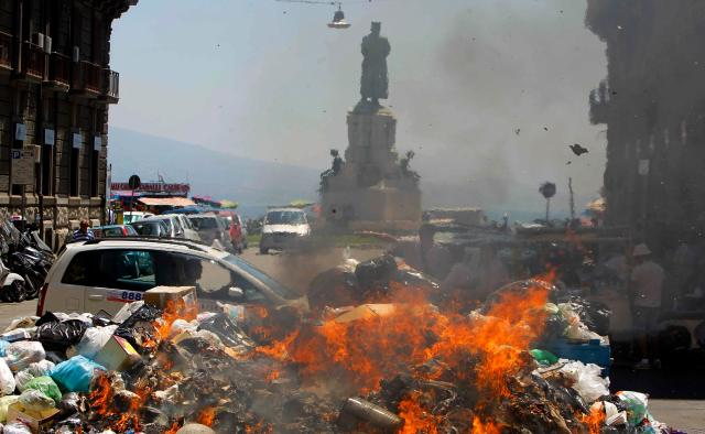 Rubbish is set on fire during a protest in downtown Naples